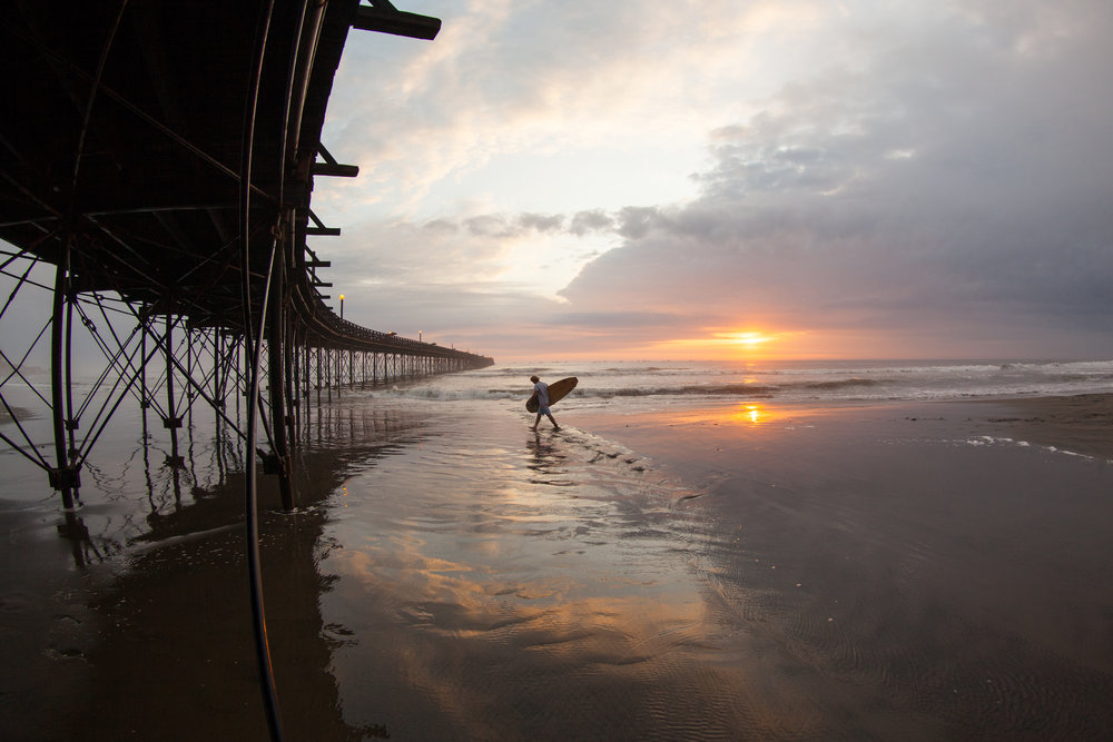 A surfer walks along the beach in Chiclayo with it's interesting curved pier whilst the sun sets over the ocean behind.