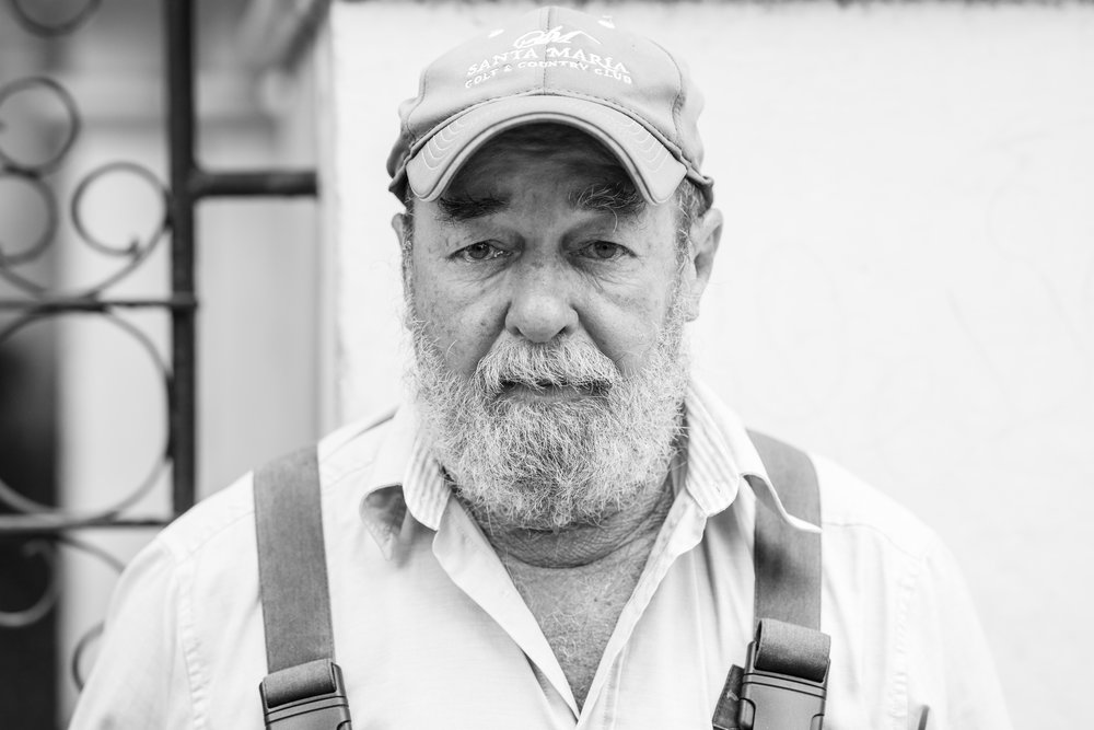 A black and white street portrait of a man in dungarees and cap in Havana, Cuba.