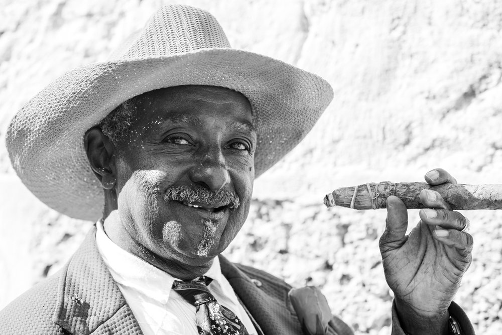 A black and white street portrait of a friendly man smoking a cigar in La Habana.