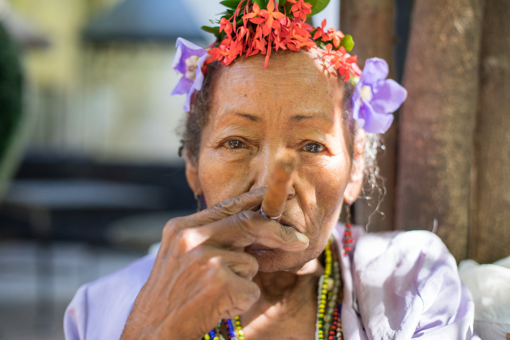 A beautiful elderly Cuban woman poses with a Cuban Cigar.