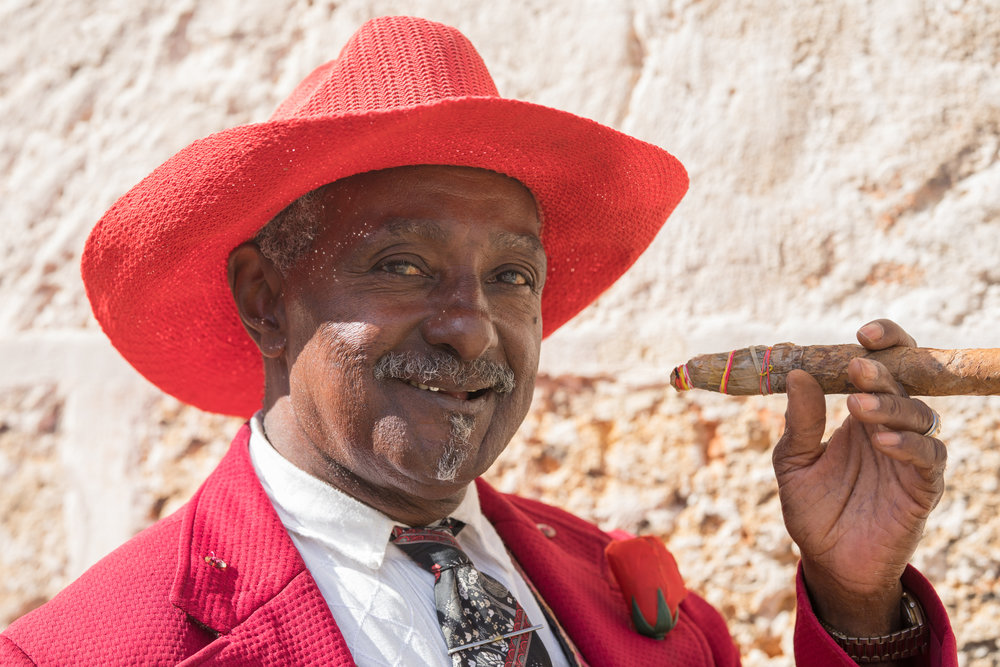 A friendly cuban in a bright red hat poses with a Cuban cigar.