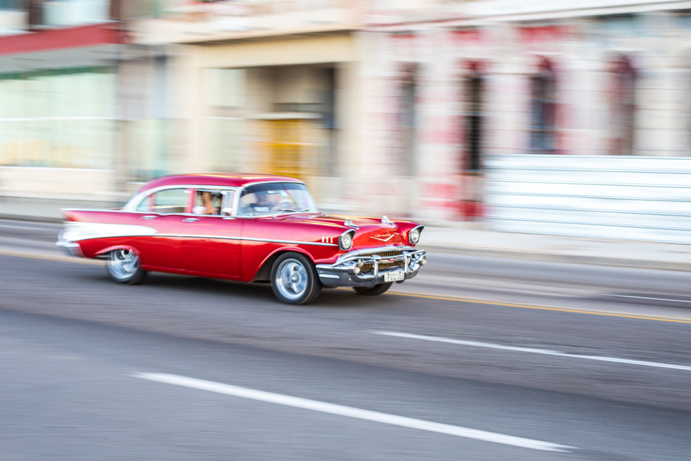 A  1957 red four door Chevrolet drives along the malecon in Havana, Cuba.