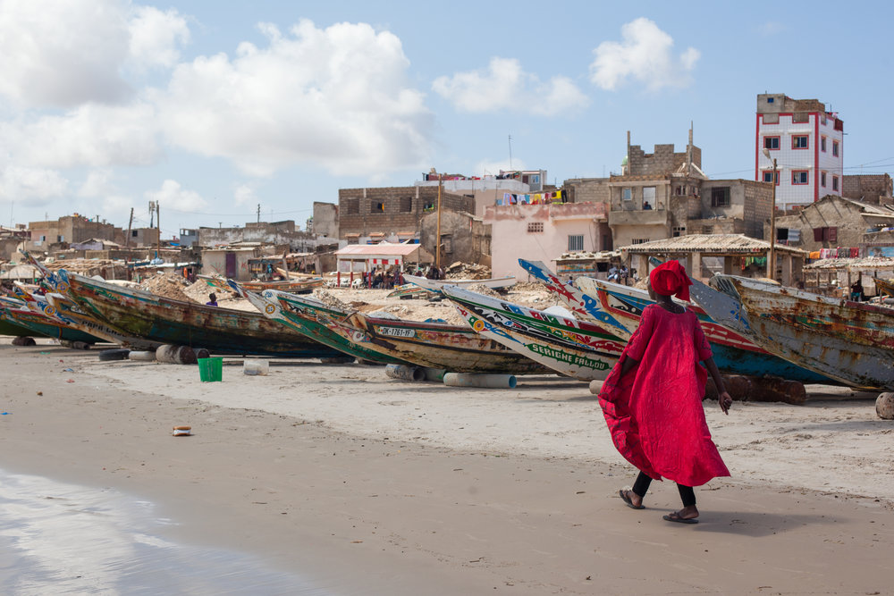 A Sengalese woman in striking African clothing walks past the fishing boats which line the beach.
