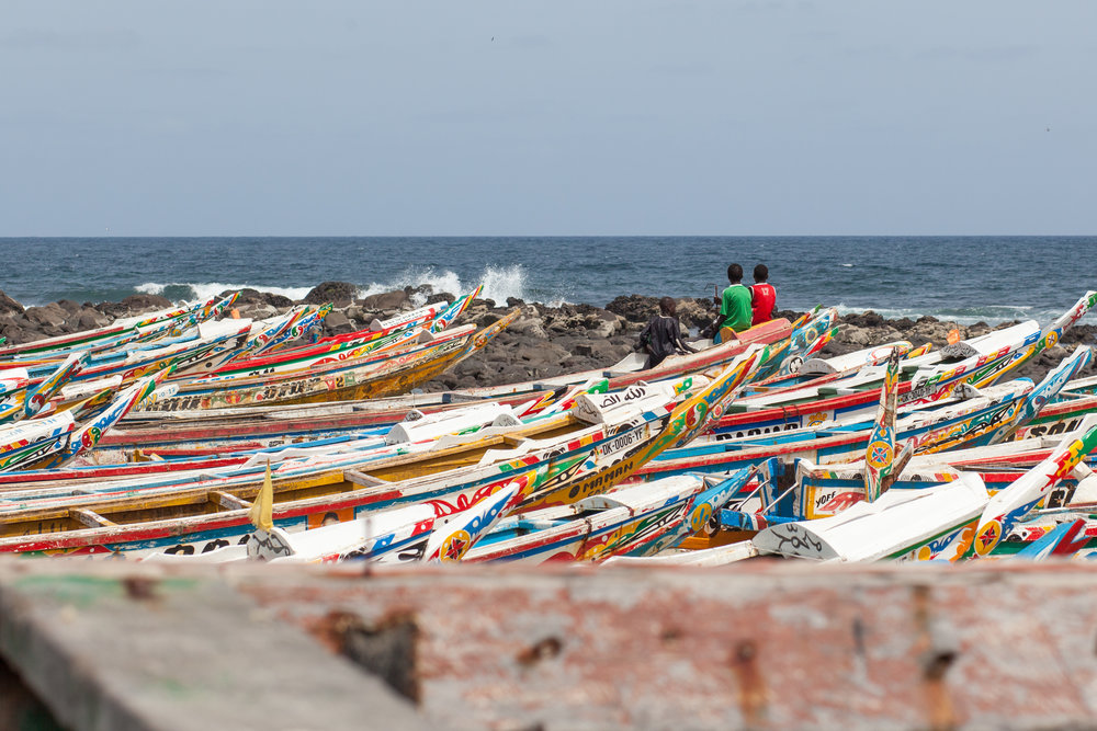 Children wearing football T-Shirts sit amongst the fishing boats at the far end of the beach at Yoff in Dakar.