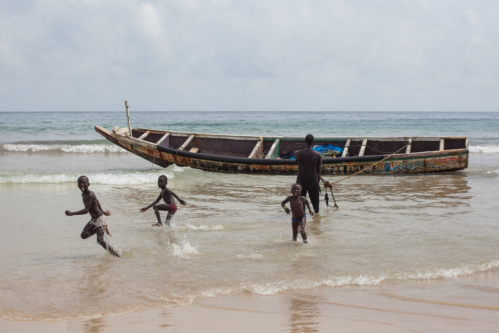 Excited African children play in the ocean as their father brings his boat back onto shore.