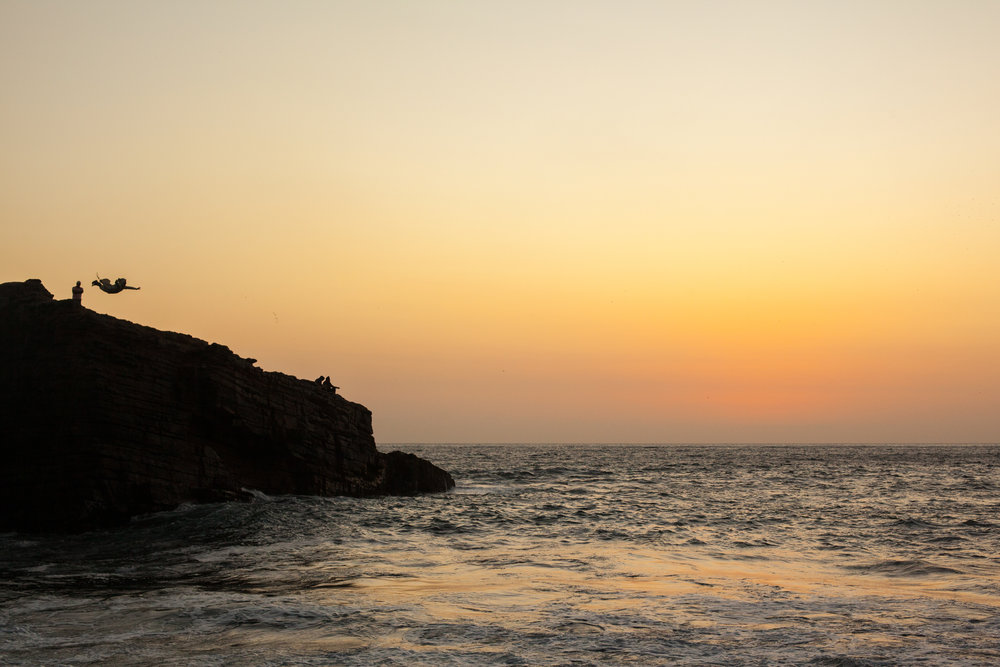 A man dressed as a monk dives into the ocean at sunset in Chorillos, Lima, Peru.