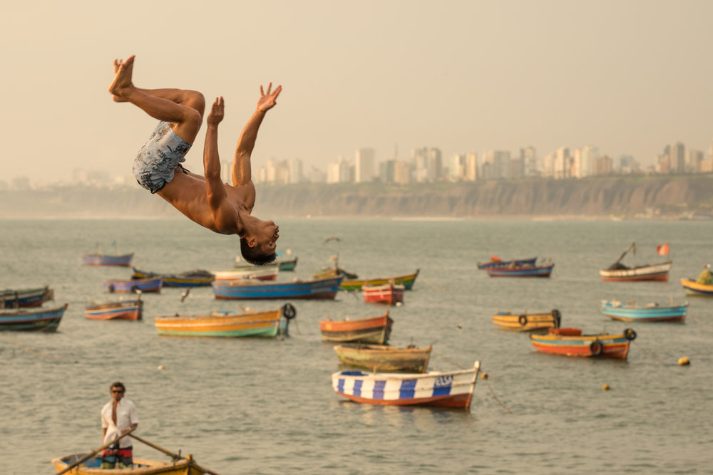 A boy backflips into the sea at Playa de Pescadores in Corillos, Lima, Peru.