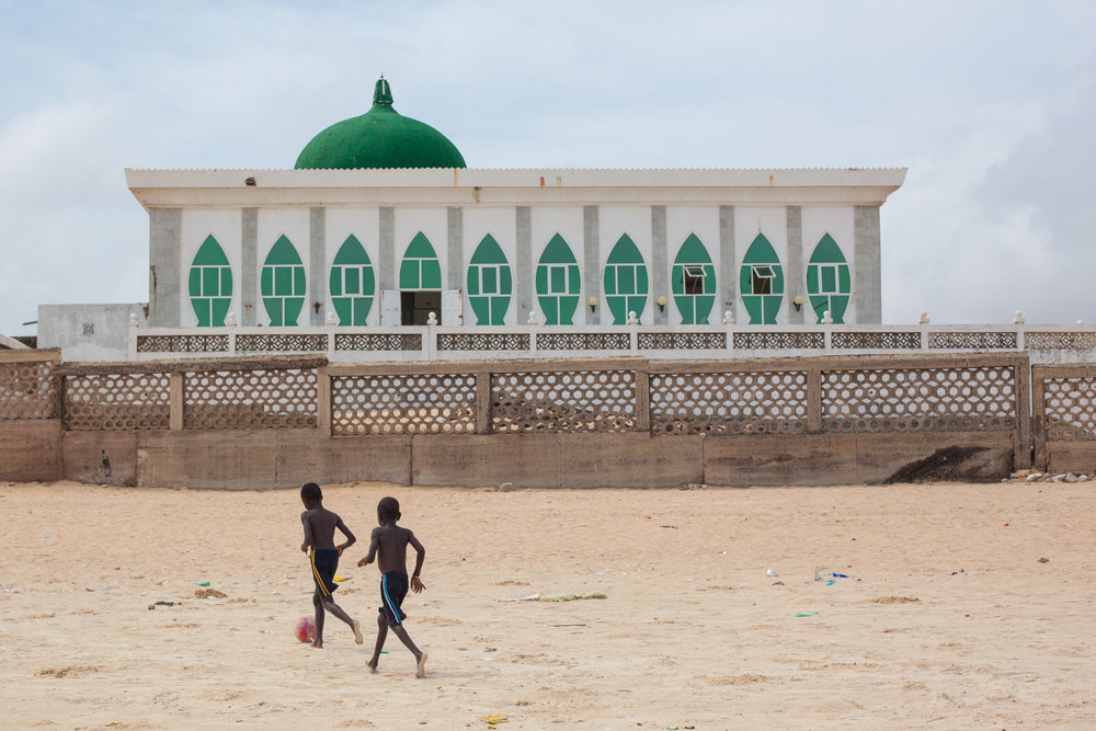 Documentary photography in Senegal.  Two boys play football in front of a mosque on the beach in Dakar.