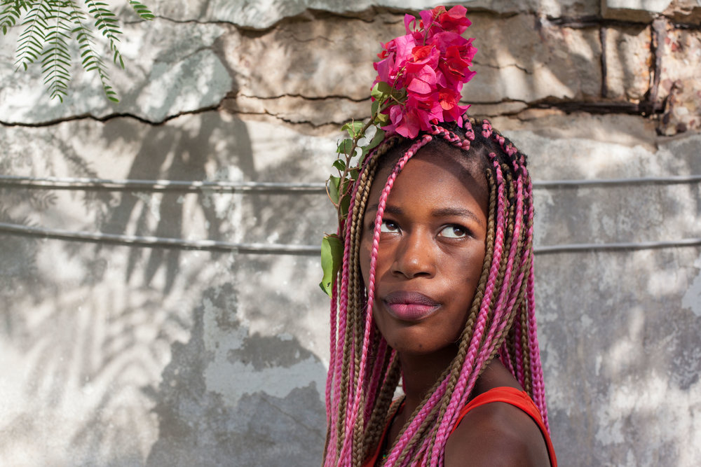A Senegalese woman poses for a photo with flowers in her hair.