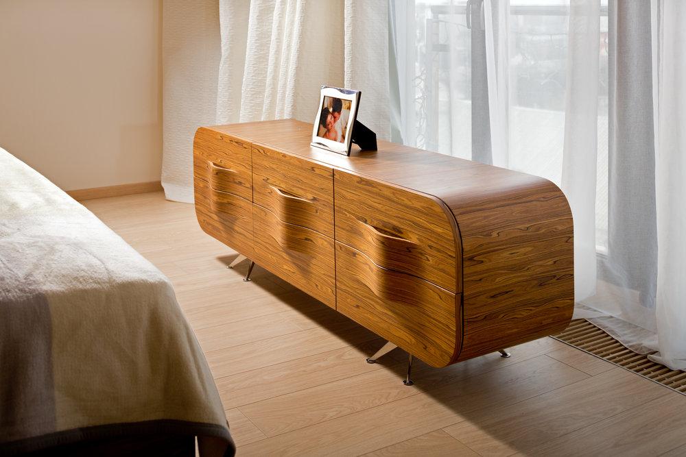 Светлый комод для спальни из дерева. Домашний текстиль пастельных цветов. Modern light wooden commode for bedroom room. Pastel color home decor.