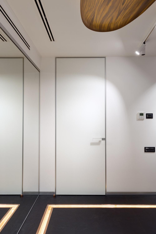 Белая дверь скрытого монтажа. White flush door and dark floor.