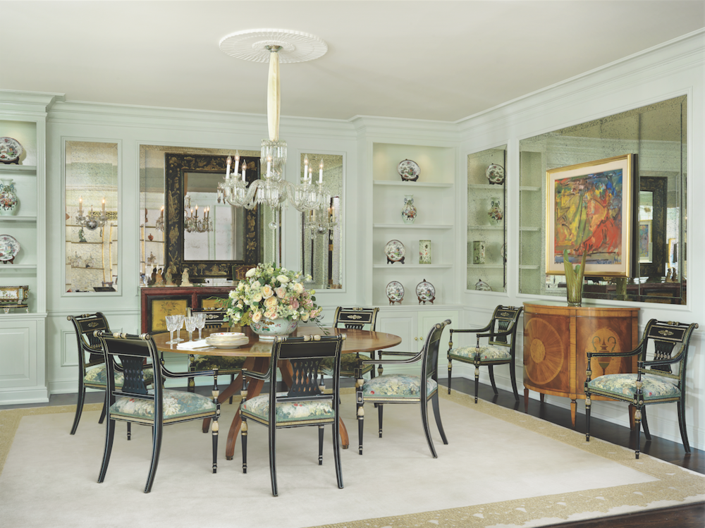 Original built-in shelving in the formal dining room was painted a soft celadon and lit from within. The lush rose centerpiece is the work of award-winning artist and floral designer Melinda Roeleveld, owner of Les Bouquets.