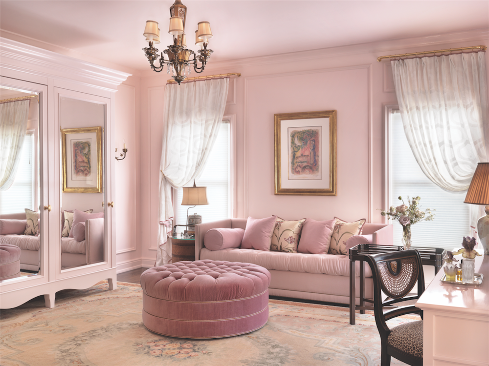 "Awash in Benjamin Moore's ""Touch of Pink,"" the dressing room features a custom armoire, grosgrain-trimmed window treatments on brass rods, and a treasured Chagall."
