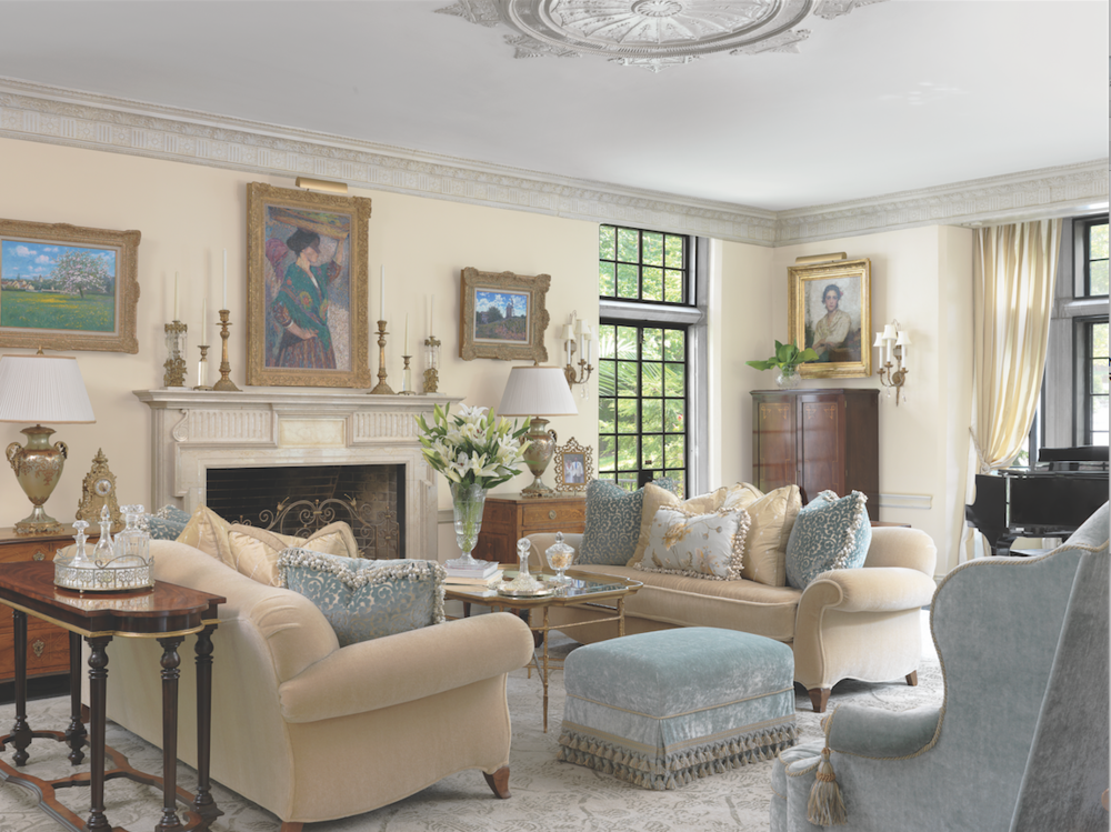 A palette of creamy whites on walls and crown molding is continued into fabrics and trims, with soft blue upholstery on Queen Anne chairs, pillows and a tasseled ottoman.
