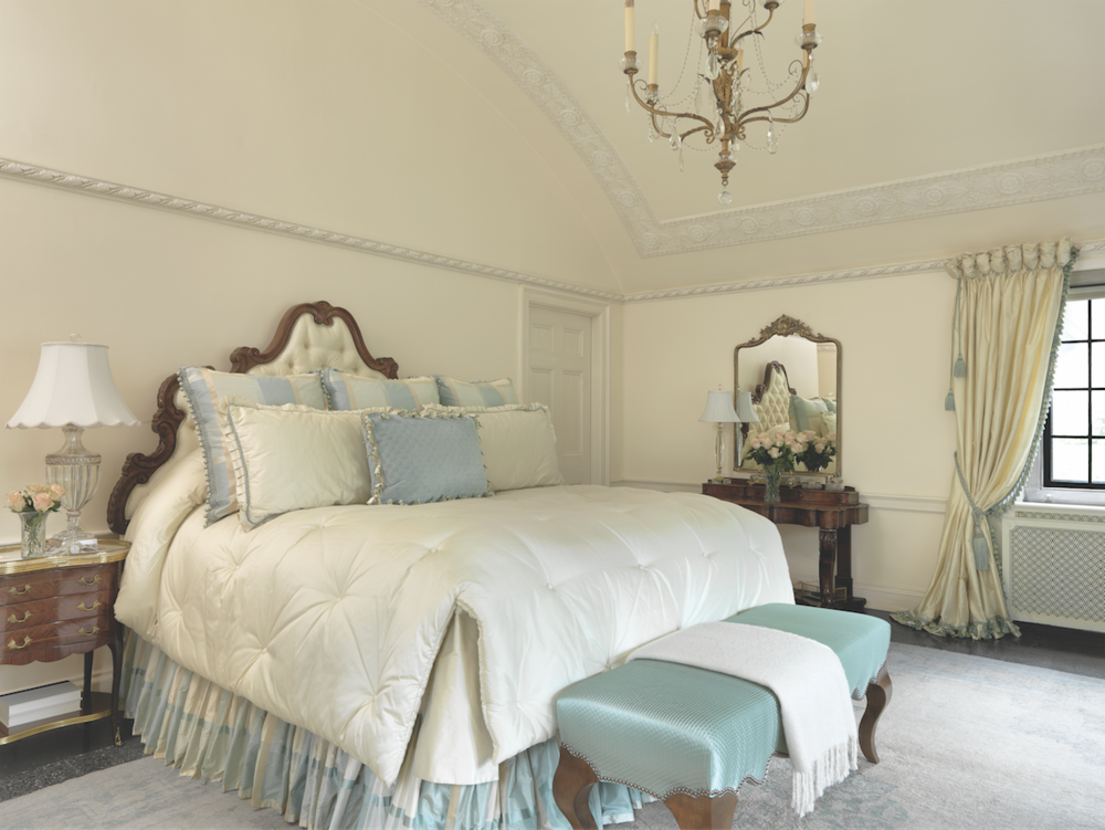 Bespoke linens, puddled draperies, and a richly padded headboard create a romantic ambience in the barrel-ceilinged master bedroom.