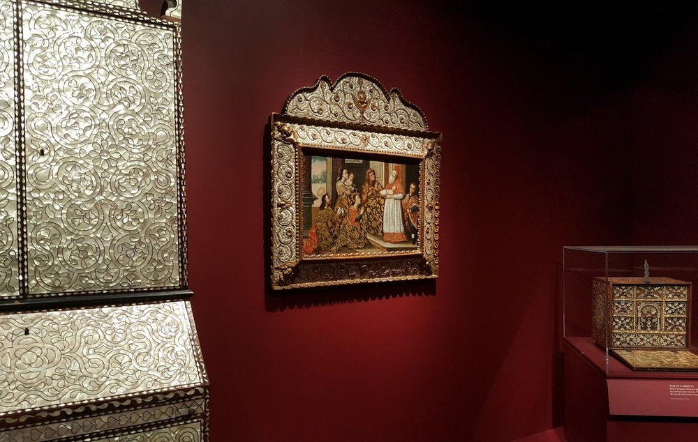 We were pleased to see that one of our alumni is included in the exhibition, an eighteenth-century Peruvian painting in an extraordinary shell encrusted frame, acquired from us by the Hispanic Society of America.  It appears in the center of this view of one corner of the exhibition.