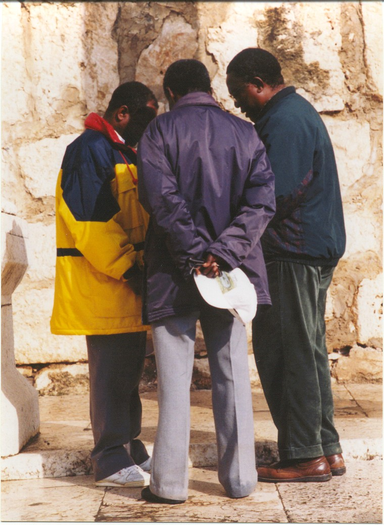 African priests, praying at every site.jpg