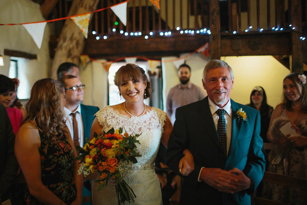 Bride and father walk down the aisle at Craven Arms Cruck Barn wedding
