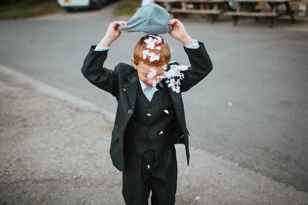 Young boy tips confetti on his head at a Yorkshire wedding