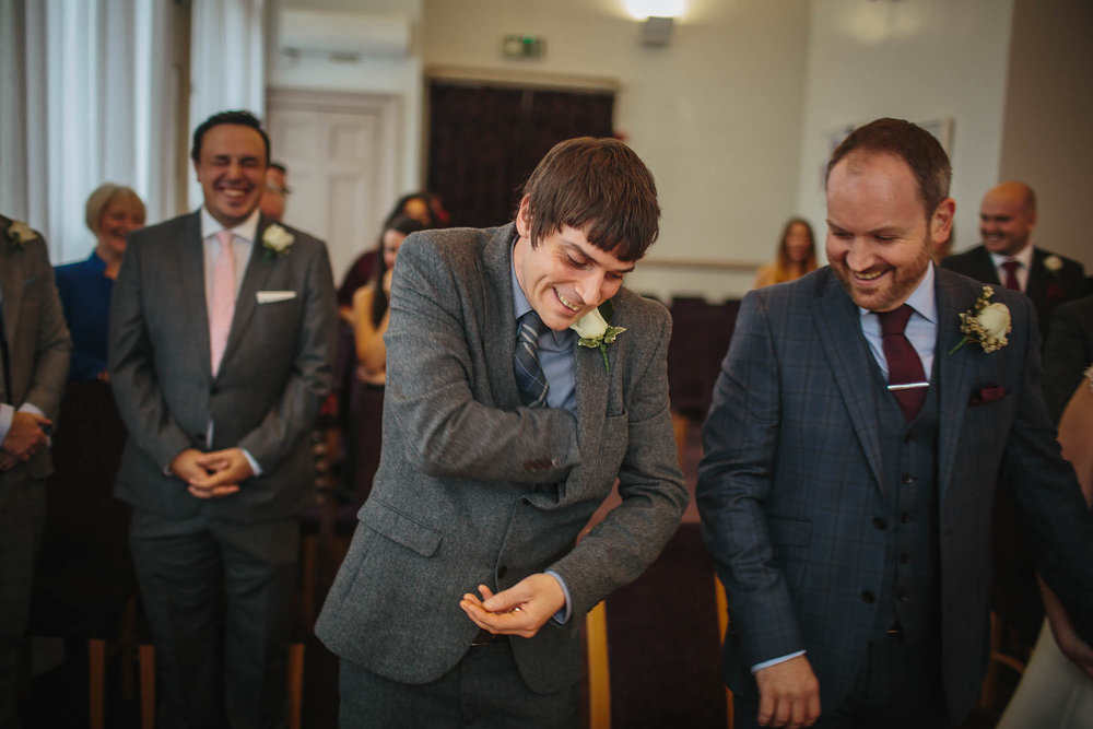 Best man reaches for the ring at a wedding ceremony in Leeds Yorkshire