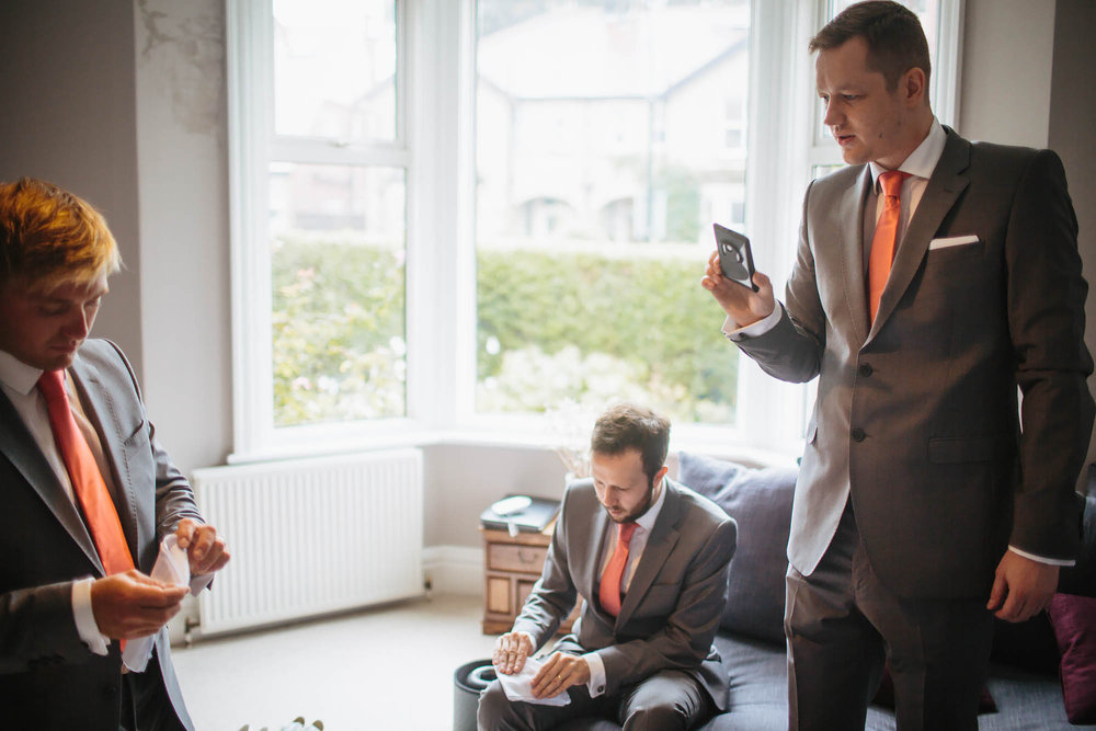 Groomsmen looking at their phones and folding pocket squares