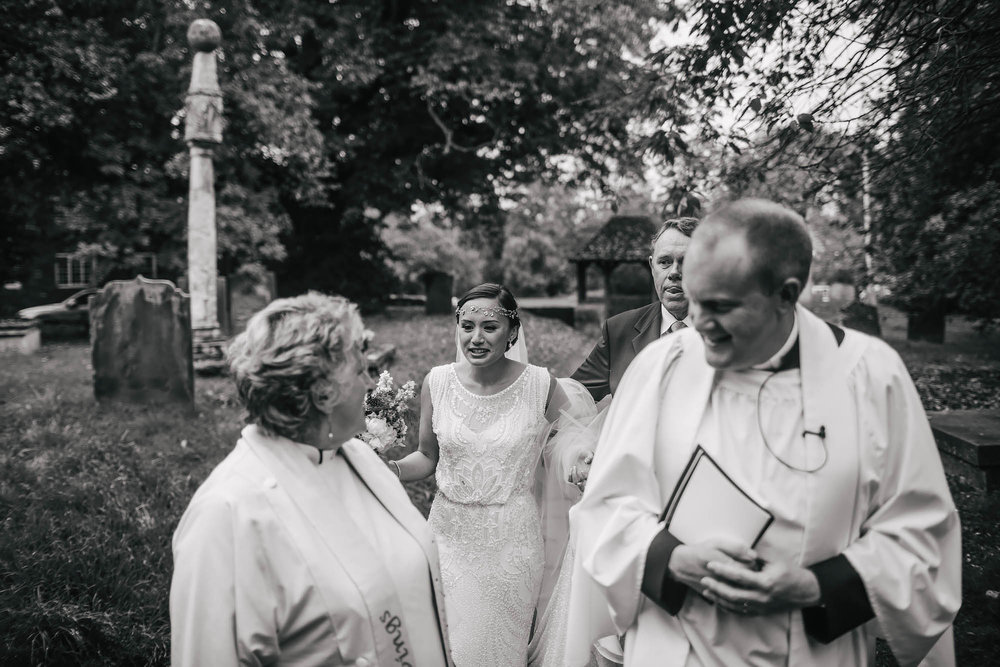 Bride talking with the vicars at the church on her wedding day in Yorkshire