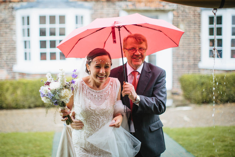 Bride and father under an umbrella in the rain