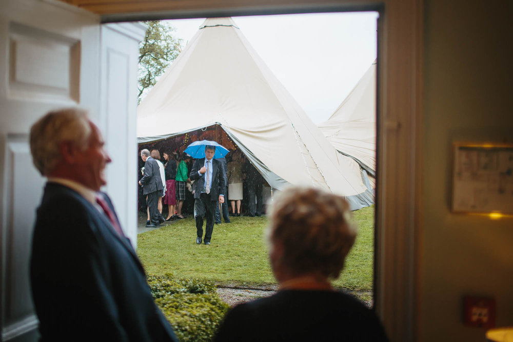 Guests laughing at a man with an umbrella at a wedding