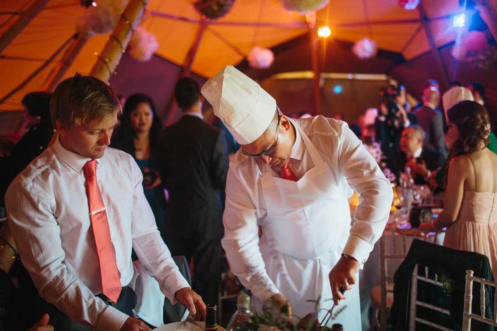 Guests carving meat at the table in a chefs hat at a tipi wedding