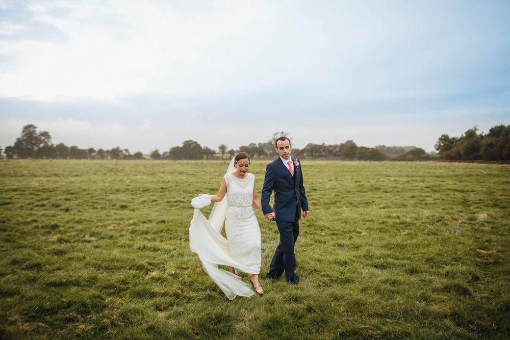Bride and groom walking through a field at Hornington Manor