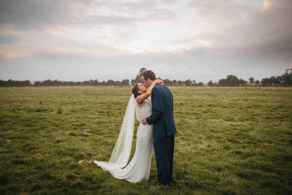 Bride and groom kissing in a field at Hornington Manor