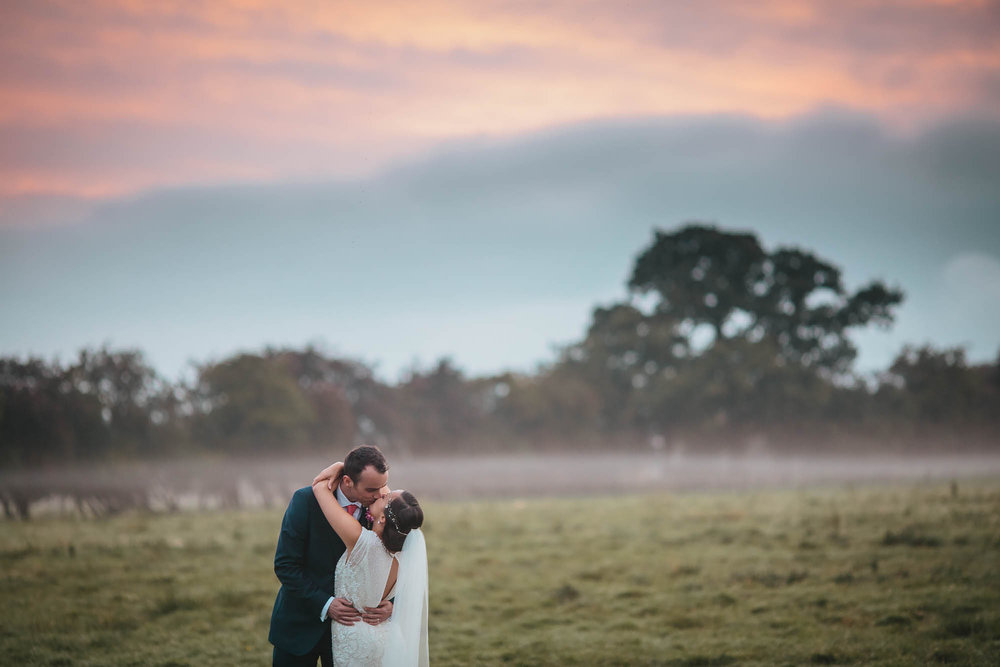 Bride and groom kissing in front of a sunset at a Hornington Manor wedding