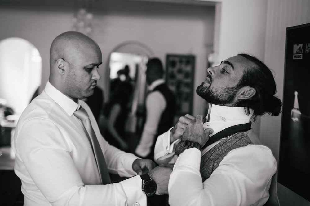 Best man helps groom with his tie during wedding prep