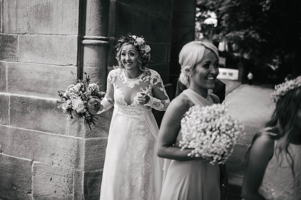 Bride laughing outside the church on her wedding day