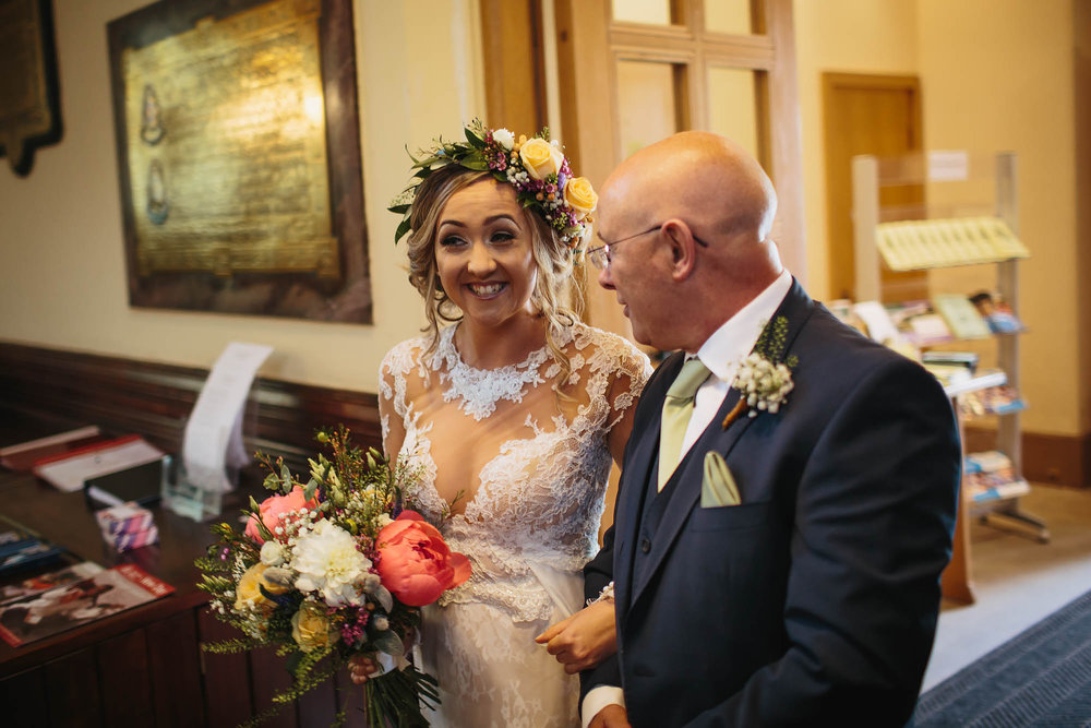 Bride laughing as her father walks her down the aisle at the church