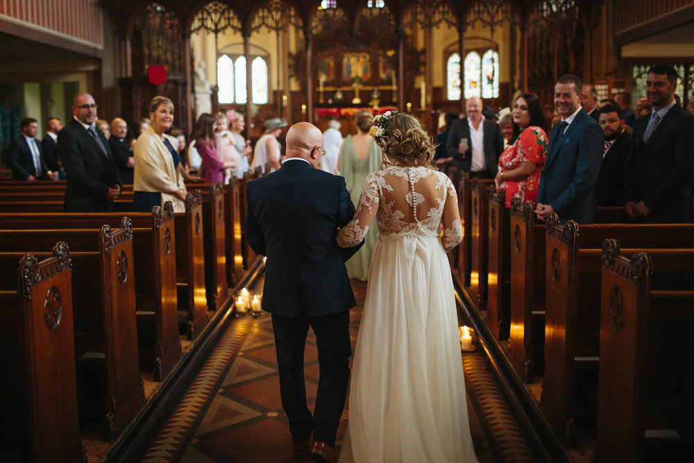 Bride and father walk down the aisle of the church on her wedding day in Manchester