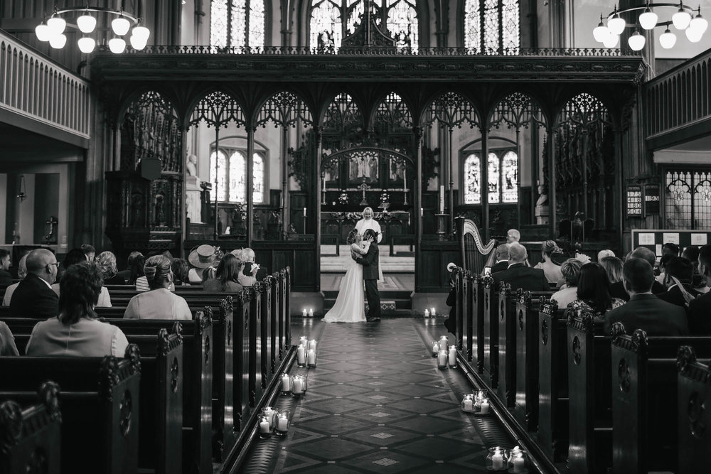 Bride and groom share their first kiss at the church on their wedding day
