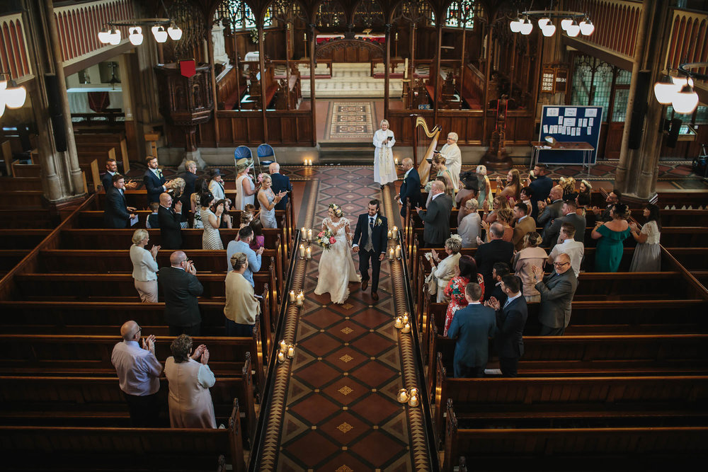 Bride and groom walk down the church aisle as a married couple