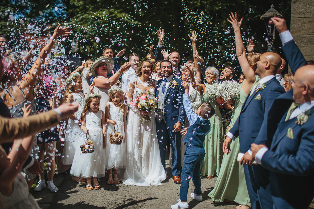 Wedding guests throw confetti over the bride and groom