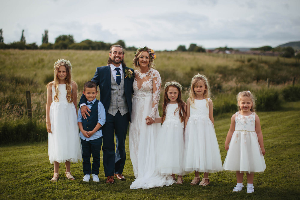 Bride groom and bridesmaids pose for a photo at a wedding