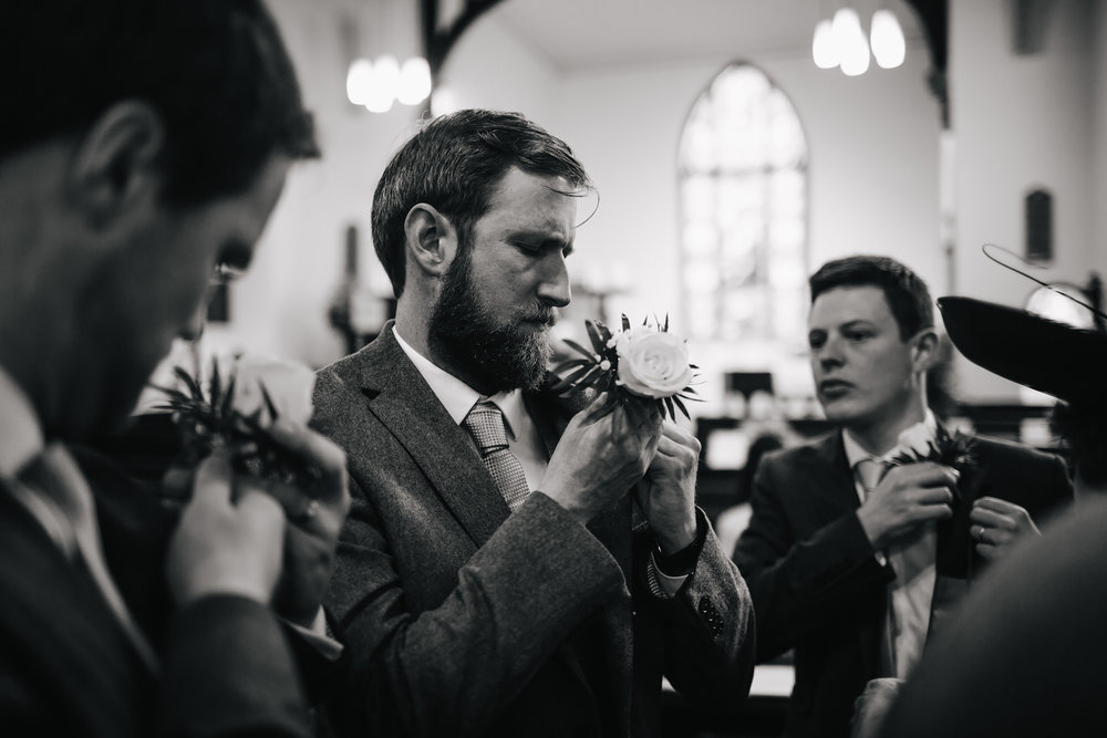 Groomsmen putting in their buttonholes in Lancashire