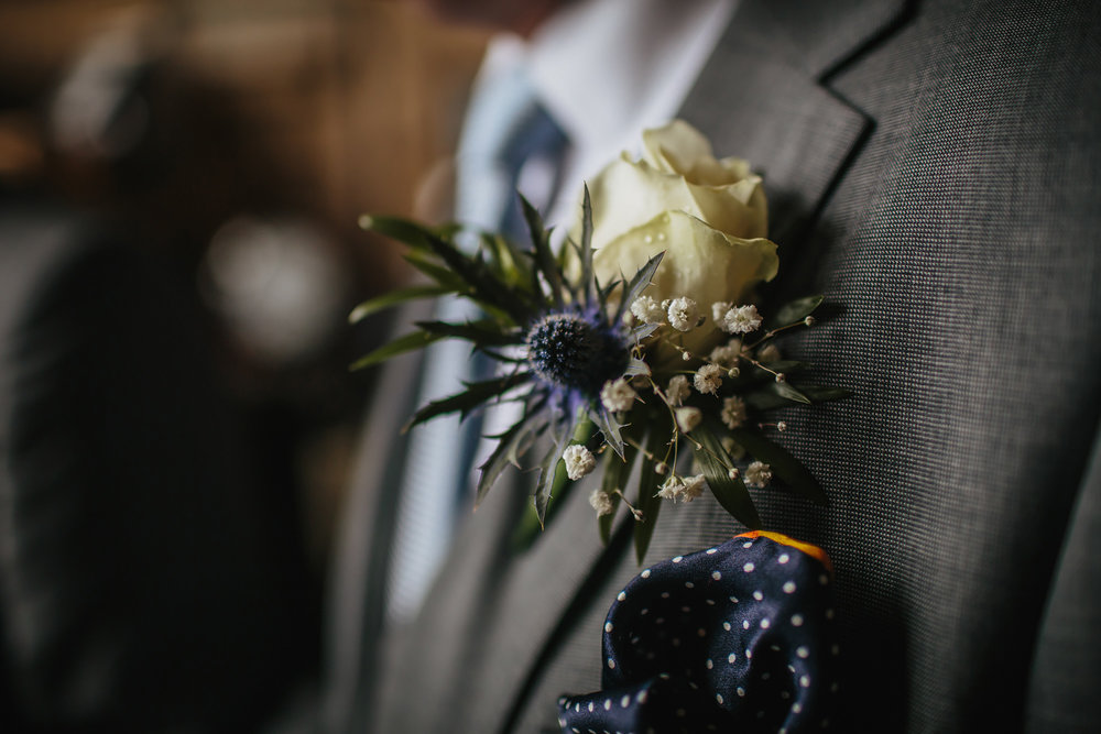 A close up of the grooms buttonhole on his suit