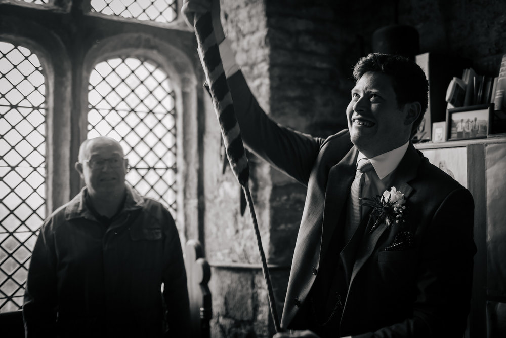Groom ringing the church bell on his wedding day
