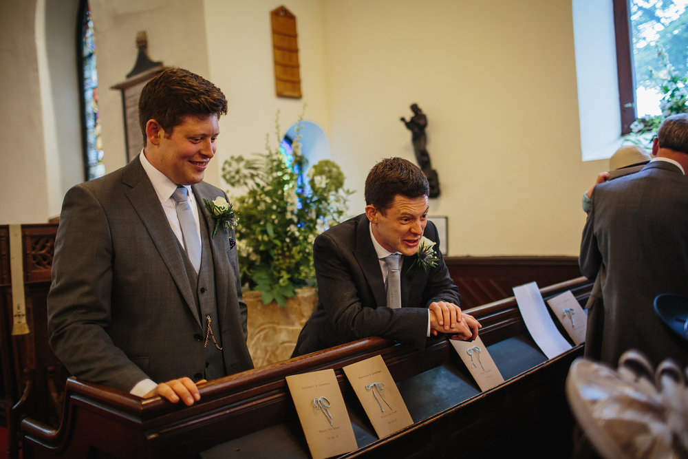 Groom and best man laughing at the church at a wedding