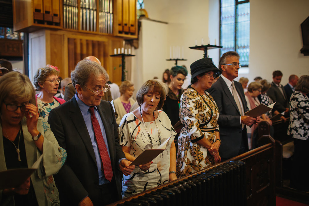 Wedding guests singing hymns in the church ceremony
