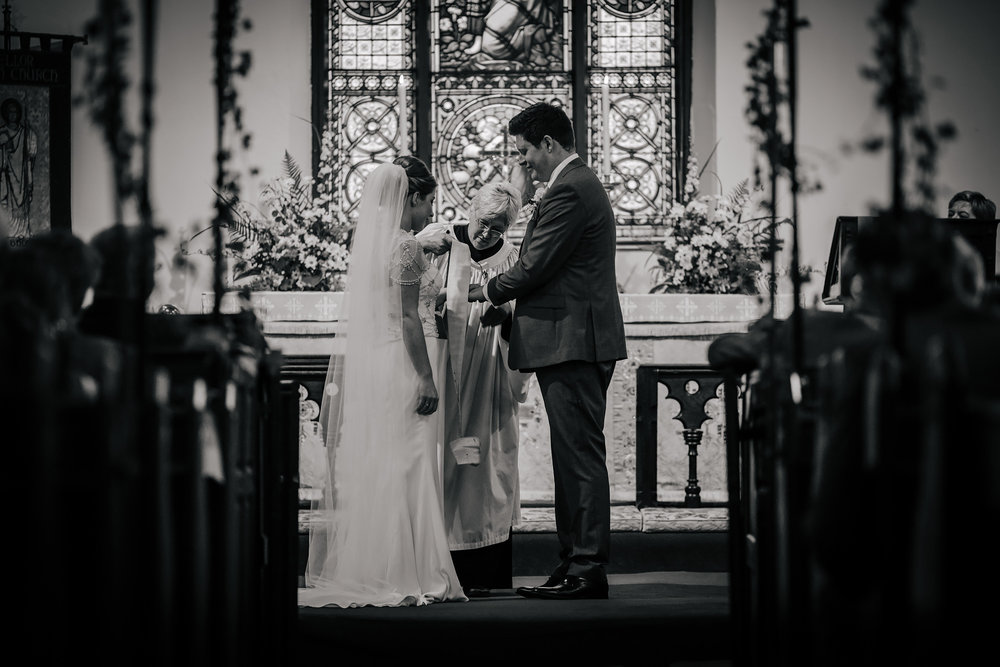 Vicar tying hands of the bride and groom during the wedding ceremony
