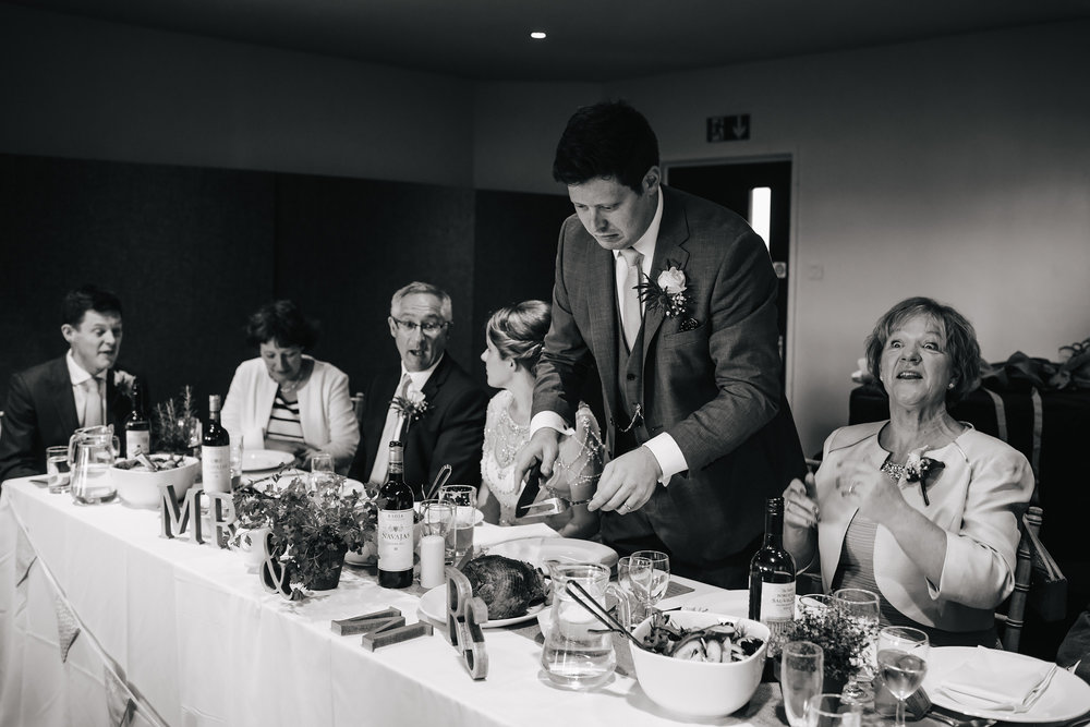 Groom carving meat at the top table on his wedding day