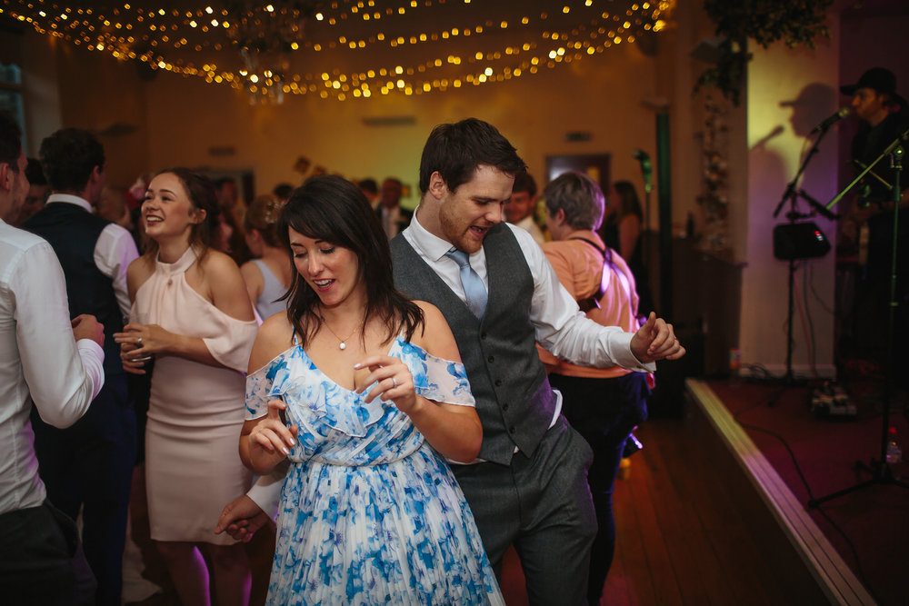 Guests dancing to a live band at a wedding