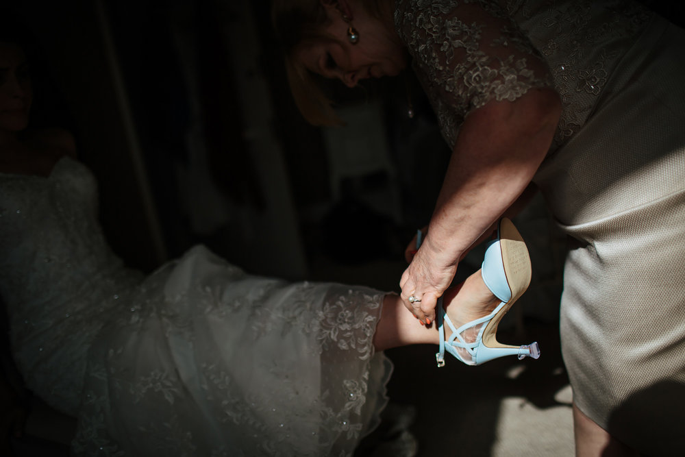 Mother helping bride put her wedding shoes on