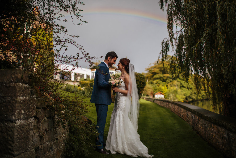 Bride and groom portrait in front of rainbow